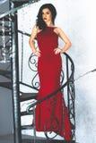 Junger vorbildlicher Brunette in der roten Kleideraufstellung Lizenzfreies Stockfoto