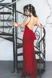 Junger vorbildlicher Brunette in der roten Kleideraufstellung Stockfoto
