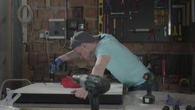 Junger Vorlageningenieur gerichtet auf die Bohrung eines Lochs mit Werkzeug auf dem Hintergrund einer kleinen Werkstatt mit Instr stock video
