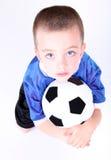 Junger Vorschuljunge, der auf eine Fußballkugel legt Lizenzfreie Stockbilder
