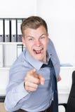 Junger wütender Mann zeigt mit seinem Finger im Büro Lizenzfreie Stockfotos