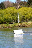 Junger Wakeboarder, der weg von einem Sprung am Kabelpark groß geht Stockfoto