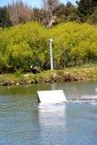 Junger Wakeboarder, der weg von einem Sprung am Kabelpark groß geht Stockfotos