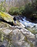 Junger Wanderer in dem Fluss Stockbild
