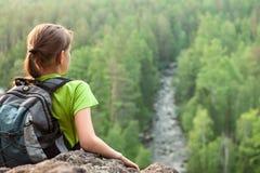 Junger Wanderer, der den Abstand von der Bergspitze untersucht Lizenzfreie Stockbilder