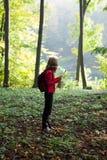 Junger Wanderer las die Karte im sonnigen grünen Wald lizenzfreies stockfoto