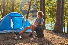 Junger Wandererkerl mit dem gelockten Haar, das auf einem Stuhl am Lager im Wald sitzt stockbilder