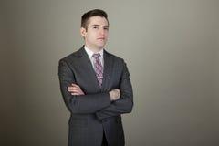 Junger weißer Geschäftsmann in einer Reihe mit den Armen gefaltet Stockbilder