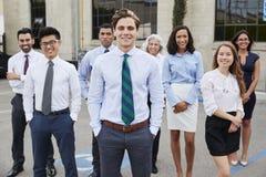 Junger weißer Geschäftsmann und Kollegen draußen, Porträt lizenzfreie stockfotos