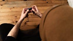Junger weißer Kerl, der zu Hause Videospiel mit einem Steuerknüppel in einer Couch und in einem orange Hut spielt lizenzfreie stockbilder