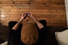 Junger weißer Kerl, der zu Hause Videospiel mit einem Steuerknüppel in einer Couch und in einem orange Hut spielt lizenzfreie stockfotos