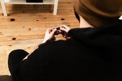 Junger weißer Kerl, der zu Hause Videospiel mit einem Steuerknüppel in einer Couch und in einem orange Hut spielt stockfotos