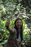 junger weißer Mädchenreisender mit dem blauen Zopfhaar im Dschungel, der eine Machete hält lizenzfreie stockbilder