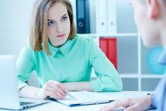 Junger weiblicher Angestellter der Stellenbesetzungsagentur hilft, die Form zum männlichen Arbeitssuchenden zu ergänzen Geschäft, stockfoto