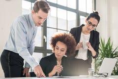 Junger weiblicher Angestellter, der um Rat ihr erfahrenes colleagu bittet Stockfotos