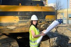 Junger weiblicher Architekt an der Baustelle des Bauvorhabens Lizenzfreies Stockfoto