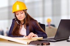 Junger weiblicher Architekt, der Pläne studiert Lizenzfreie Stockfotos
