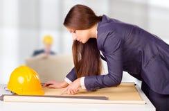 Junger weiblicher Architekt, der Pläne studiert Stockbilder