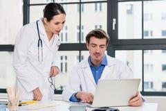 Junger weiblicher Arzt, der um Rat von ihrem erfahrenen männlichen Kollegen bittet Stockfotos