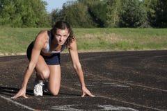 Junger weiblicher Athlet ist zum Rennen betriebsbereit. Lizenzfreie Stockfotografie