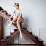 Junger weiblicher Balletttänzer in der blauen Klage, die auf Treppe sitzt stockfotografie