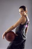 Junger weiblicher Basketball-Spieler, der auf grauem Hintergrund aufwirft lizenzfreie stockfotografie