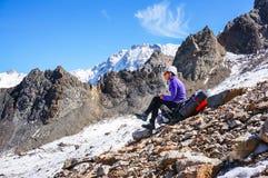 Junger weiblicher Bergsteiger in einem stillstehenden Sitzen des Sturzhelms auf einem Rucksack und schreibt den geführten Weg Stockfoto