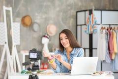 Junger weiblicher Blogger mit dem Zubehör, das Video notiert Stockbilder