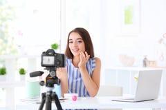 Junger weiblicher Blogger mit den Kosmetik, die Video notieren Stockbild