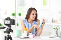 Junger weiblicher Blogger mit den Kosmetik, die Video notieren Lizenzfreies Stockbild