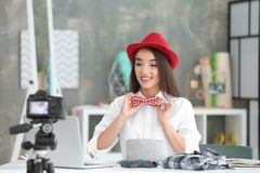 Junger weiblicher Blogger mit Hut- und Fliegenaufnahmevideo Stockbilder