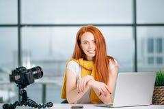 Junger weiblicher Blogger mit Laptop und Buch auf Kamera sortieren das Betrachten der Kamera aus Lizenzfreie Stockfotografie