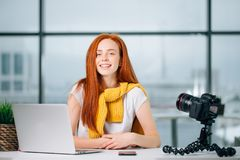 Junger weiblicher Blogger mit Laptop und Buch auf Kamera sortieren das Betrachten der Kamera aus Stockfotografie