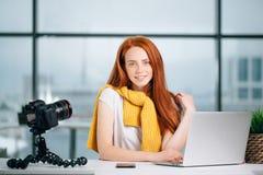 Junger weiblicher Blogger mit Laptop und Buch auf Kamera sortieren das Betrachten der Kamera aus Lizenzfreie Stockfotos