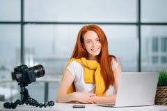 Junger weiblicher Blogger mit Laptop und Buch auf Kamera sortieren das Betrachten der Kamera aus Lizenzfreies Stockfoto