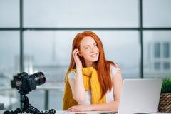 Junger weiblicher Blogger mit Laptop und Buch auf Kamera sortieren das Betrachten der Kamera aus Stockfoto