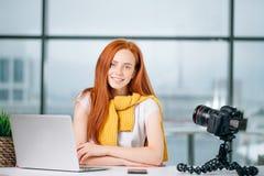 Junger weiblicher Blogger mit Laptop und Buch auf Kamera sortieren das Betrachten der Kamera aus Lizenzfreies Stockbild