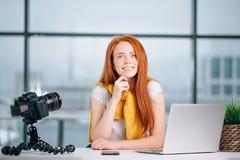 Junger weiblicher Blogger mit Laptop und Buch auf Kamera sortieren das Betrachten der Kamera aus Stockfotos