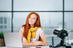 Junger weiblicher Blogger mit Laptop und Buch auf Kamera sortieren das Betrachten der Kamera aus Stockbild