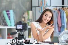 Junger weiblicher Blogger mit Make-upkosmetik Stockbilder