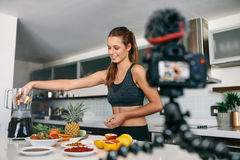 Junger weiblicher Bloggeraufnahmeinhalt für videoblog in der Küche Lizenzfreie Stockfotos