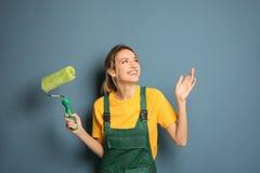 Junger weiblicher Dekorateur mit Farbenrolle stockbilder