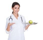 Junger weiblicher Doktor Presenting Green Apple Lizenzfreies Stockfoto