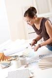 Junger weiblicher Entwerfer, der mit Farbenmustern arbeitet Lizenzfreie Stockfotos