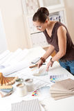 Junger weiblicher Entwerfer, der mit Farbenmustern arbeitet Stockbild