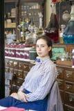 Junger weiblicher Fachverkäufer, der sich im viktorianischen Chemiker hinsetzt Lizenzfreies Stockbild