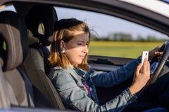 Junger weiblicher Fahrer, der eine Textnachricht liest lizenzfreies stockbild