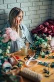 Junger weiblicher Florist, der am Telefon spricht und Anmerkungen am Blumenladen macht Lizenzfreie Stockfotografie