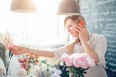 Junger weiblicher Florist, der am Telefon spricht und Anmerkungen am Blumenladen macht Lizenzfreies Stockfoto