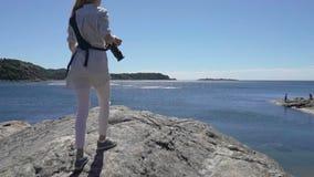 Junger weiblicher Fotograf klettert eine Klippe über dem Meer, um ein Foto zu machen stock video